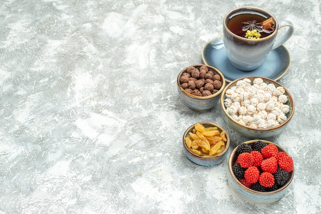 Vorderansicht tasse tee mit verschiedenen bonbons auf weißem raum