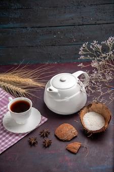 Vorderansicht tasse tee mit wasserkocher auf der dunklen oberfläche tee trinken fruchtfarbe