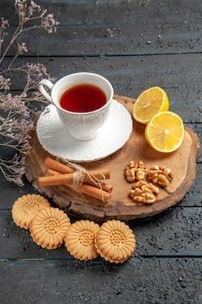 Vorderansicht tasse tee mit zitrone und keksen auf dunklem hintergrund