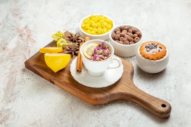 Vorderansicht tasse tee mit zitronenscheiben und bonbons auf weißem raum