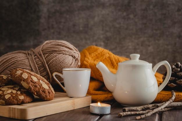 Vorderansicht tasse und teekanne mit keksen und garn
