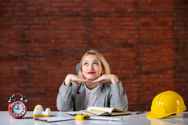Vorderansicht träumende ingenieurin, die hinter ihrem arbeitsplatz sitzt