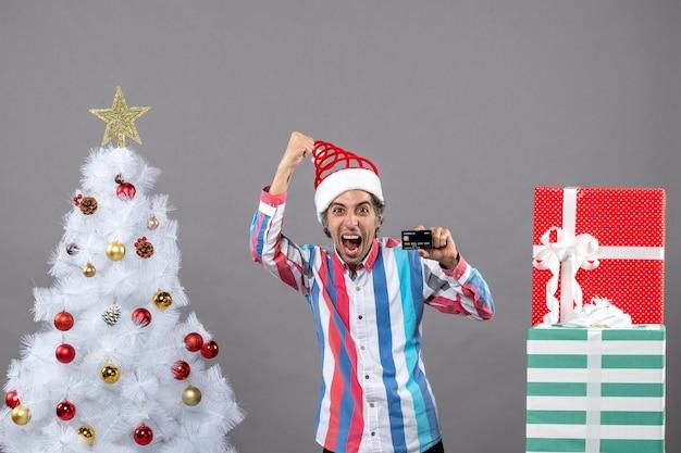 Vorderansicht überglücklicher mann in einer siegreichen geste, die nahe weihnachtsbaum steht