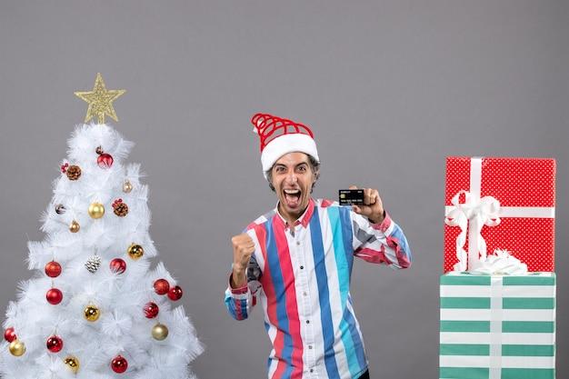 Vorderansicht überglücklicher mann in einer siegreichen geste, die nahe weißem weihnachtsbaum steht