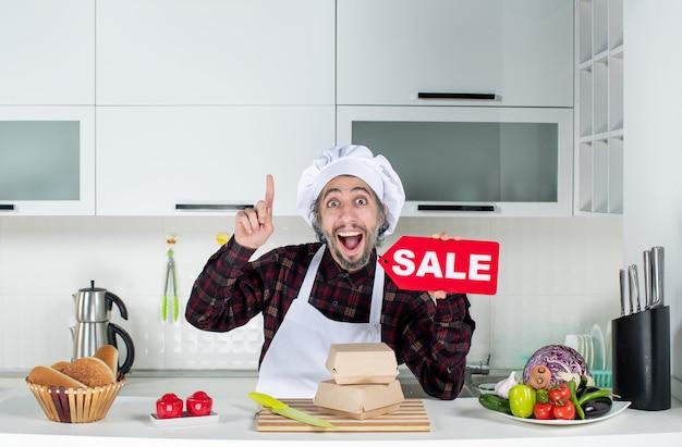 Vorderansicht überrascht männlicher koch in uniform, der auf die decke zeigt und das rote verkaufsschild in der modernen küche hochhält
