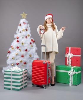 Vorderansicht überraschte blondes mädchen, das roten wecker nahe weißem weihnachtsbaum hält