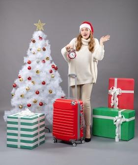 Vorderansicht überraschte blondes mädchen mit weihnachtsmütze, die roten wecker hält