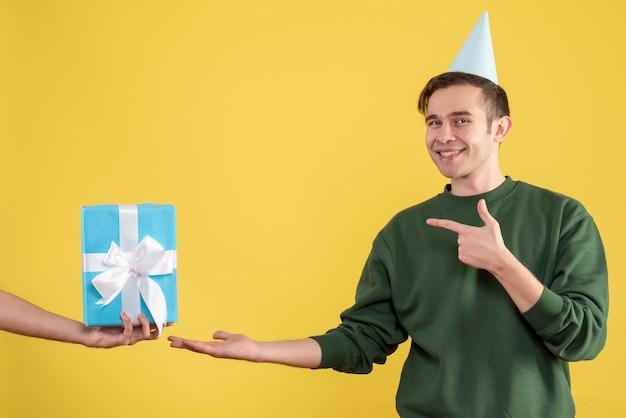 Vorderansicht überraschte jungen mann, der auf geschenk in menschlicher hand auf gelb zeigt