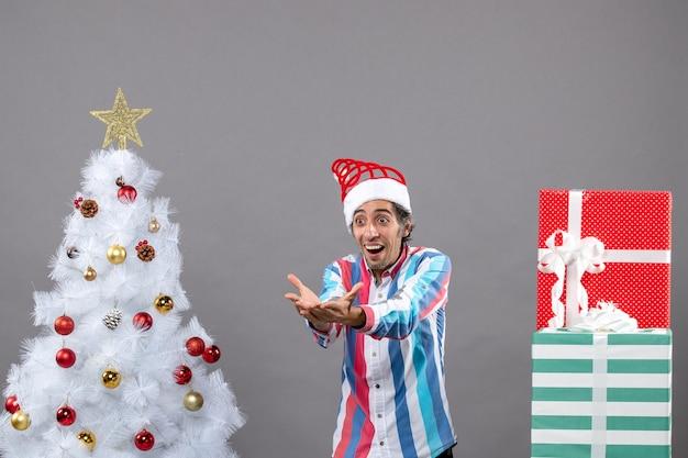 Vorderansicht überraschte jungen mann, der jemanden nahe weißem weihnachtsbaum ruft