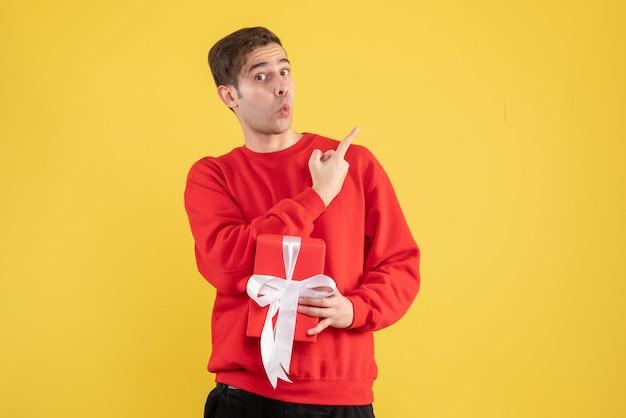Vorderansicht überraschte jungen mann mit rotem pullover, der auf gelb steht