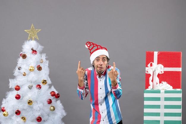 Vorderansicht überraschte jungen mannpunktfinger, der nahe weißen weihnachtsbaum zeigt