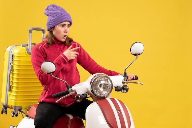 Vorderansicht überraschte junges mädchen auf moped, das auf etwas zeigt