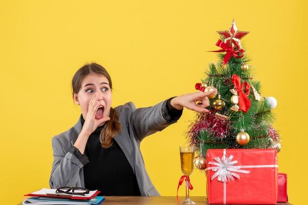Vorderansicht überraschte mädchen, das am schreibtisch sitzt und jemanden in der nähe von weihnachtsbaum und geschenkcocktail schreit und anruft