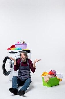 Vorderansicht überraschte männliche haushälterin, die vor waschmaschinenwäschekorb auf weißer wand sitzt