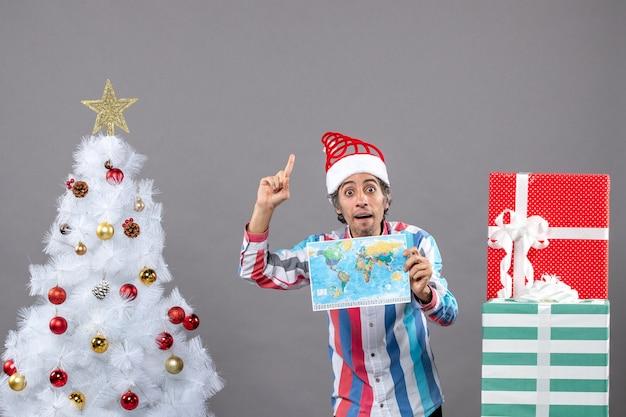 Vorderansicht überraschte mann mit spiralfeder-weihnachtsmütze, die hochhaltende weltkarte betrachtet, die hoch zeigt