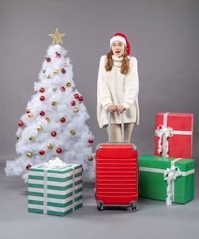 Vorderansicht überraschte weihnachtsmädchen, das valise hält, das nahe weihnachtsbaum steht