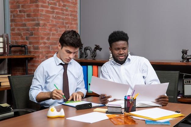 Vorderansicht unermüdliche geschäftspartner, die geschäftsverhandlungen in einem modernen büro führen