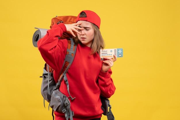 Vorderansicht verärgerte weiblichen rucksacktouristen, der flugticket hält