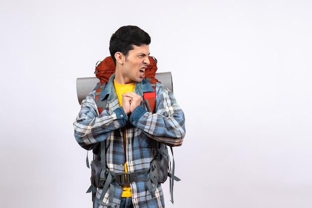 Vorderansicht verärgerter junger camper mit rucksack, der hände aneinander reibt