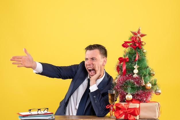 Vorderansicht verärgerter mann, der schreit, während er am tisch nahe weihnachtsbaum und geschenke auf gelbem hintergrund sitzt
