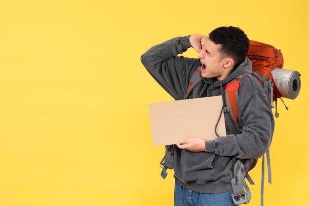 Vorderansicht verärgerter reisender mann mit rucksack, der karton hält
