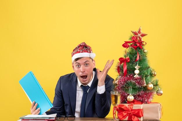 Vorderansicht verblüffter geschäftsmann, der am tisch nahe weihnachtsbaum sitzt und auf gelbem hintergrund präsentiert