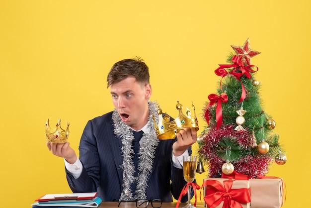Vorderansicht verblüffter geschäftsmann, der kronen betrachtet, die am tisch nahe weihnachtsbaum sitzen und auf gelbem hintergrund präsentieren