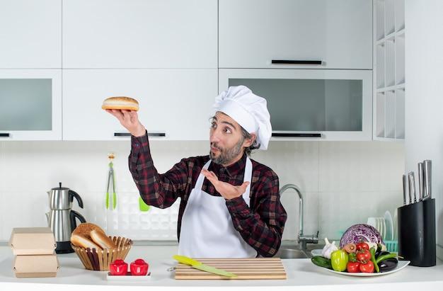 Vorderansicht verblüffter männlicher koch, der brot in der küche hochhält