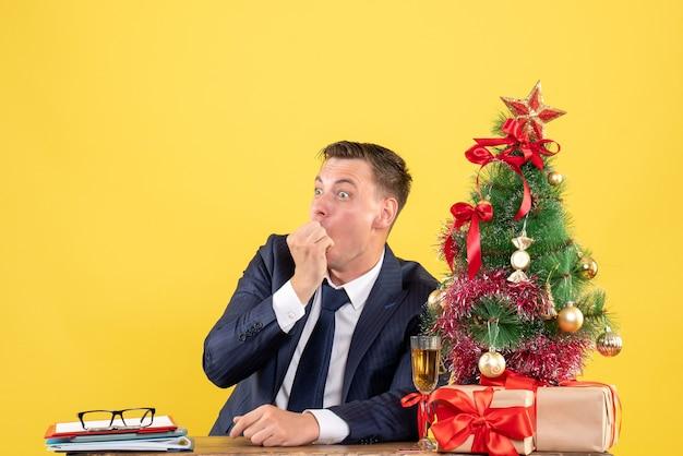 Vorderansicht verblüffter mann, der am tisch nahe weihnachtsbaum sitzt und auf gelbem hintergrund freien raum präsentiert
