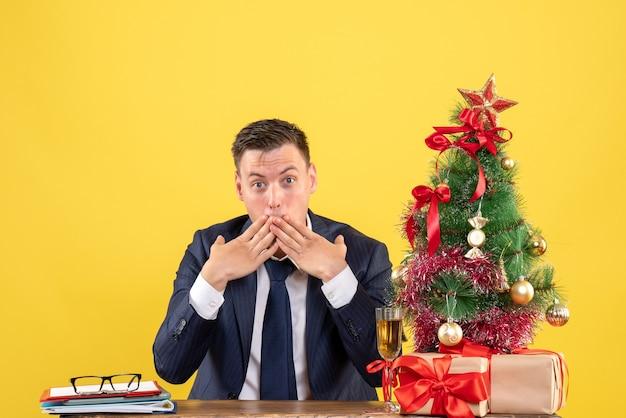 Vorderansicht verblüffter mann, der hände zu seinem mund setzt, der am tisch nahe weihnachtsbaum sitzt und auf gelbem hintergrund präsentiert