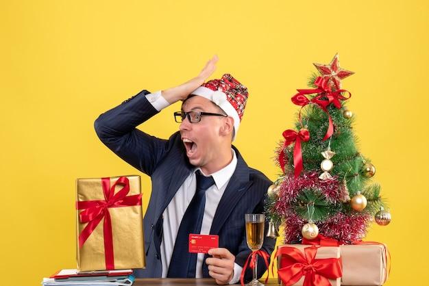 Vorderansicht verblüffter mann, der hand an seine stirn setzt, die am tisch nahe weihnachtsbaum sitzt und auf gelbem hintergrund präsentiert