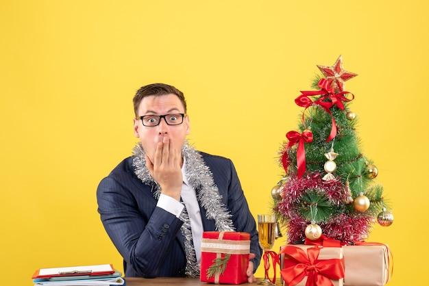 Vorderansicht verblüffter mann, der hand an seinen mund setzt, der am tisch nahe weihnachtsbaum sitzt und auf gelbem hintergrund präsentiert