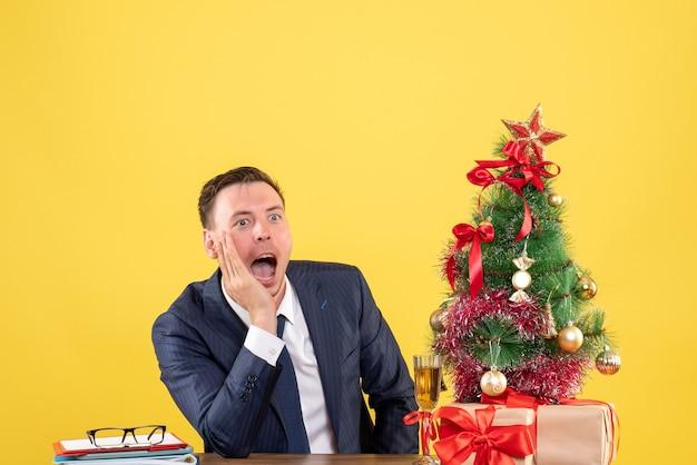 Vorderansicht verblüffter mann, der schreit, während er am tisch nahe weihnachtsbaum sitzt und auf gelbem hintergrund präsentiert