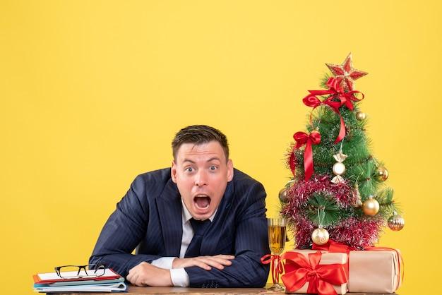Vorderansicht verblüffter mann, der seinen mund öffnet, der am tisch nahe weihnachtsbaum sitzt und auf gelbem hintergrund präsentiert