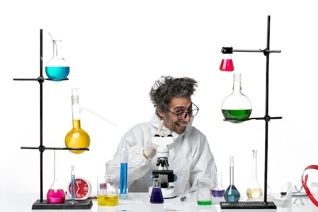 Vorderansicht verrückter männlicher wissenschaftler im speziellen schutzanzug, der um tisch mit lösungen auf weißem schreibtischlaborkrankheits-wissenschaftsvirus sitzt