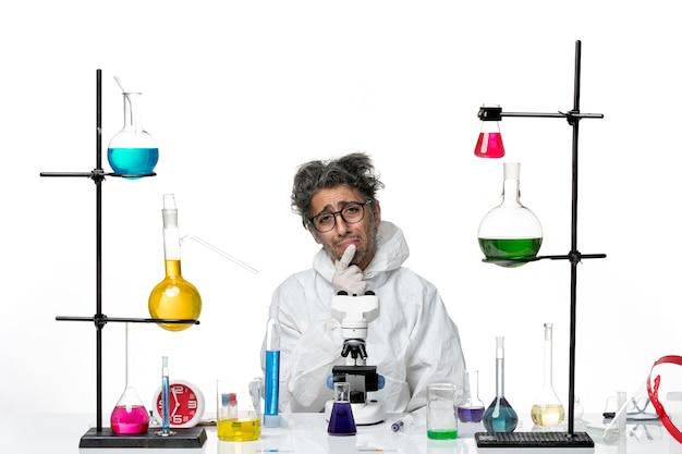 Vorderansicht verrückter männlicher wissenschaftler in speziellem schutzanzug, der um tisch mit lösungen auf weißem hintergrundlaborkrankheit-covid-wissenschaftsvirus sitzt