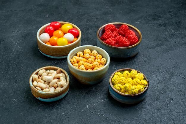 Vorderansicht verschiedene bonbons mit nüssen auf süßem zuckerkeks der süßigkeit der grauen oberfläche