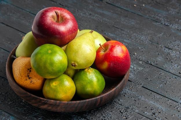 Vorderansicht verschiedene frische früchte äpfel birnen und mandarinen im teller auf dunkelblauem schreibtisch obstfarbzusammensetzung frisch reif