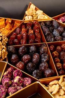 Vorderansicht verschiedene getrocknete früchte zusammen mit nüssen aller art auf dem grauen boden