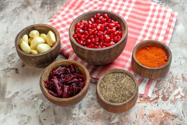 Vorderansicht verschiedene gewürze knoblauch granatäpfel und rüben auf hellem hintergrund