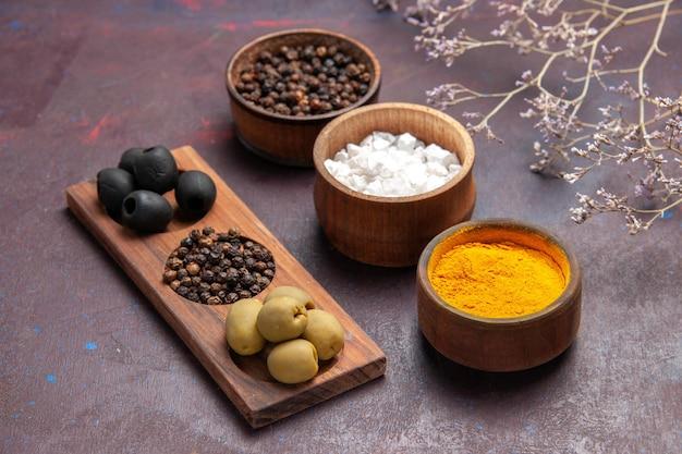 Vorderansicht verschiedene gewürze mit oliven auf dunklem raum
