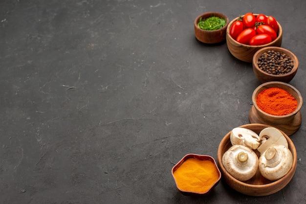 Vorderansicht verschiedene gewürze mit pilzen und tomaten auf dunklem hintergrund würziger pfeffer kantige reife farbe