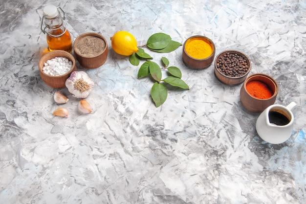 Vorderansicht verschiedene gewürze mit zitrone und knoblauch auf würzigen früchten des weißen tafelpfefferöls