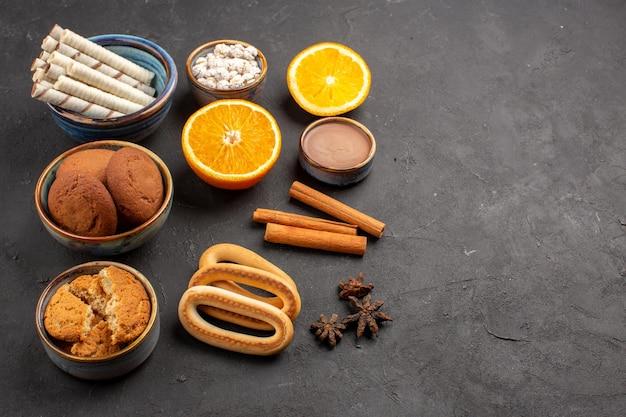 Vorderansicht verschiedene kekse mit geschnittenen orangen auf dunklem hintergrund zucker tee keks keks süße frucht