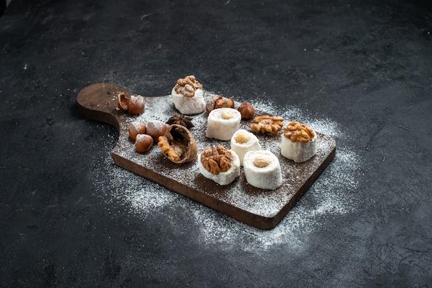 Vorderansicht verschiedene kekse mit kuchen und walnüssen auf dem dunkelgrauen oberflächenkuchen kekszucker backen süßen keks