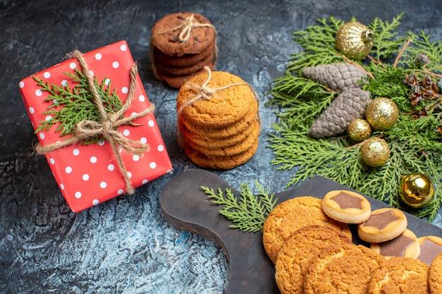 Vorderansicht verschiedene leckere kekse mit geschenk auf hell-dunkel oberfläche