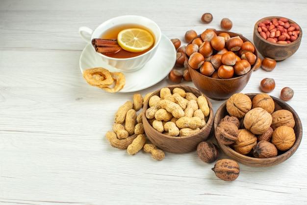 Vorderansicht verschiedene nüsse erdnüsse haselnüsse und walnüsse mit tasse tee auf weißer oberfläche
