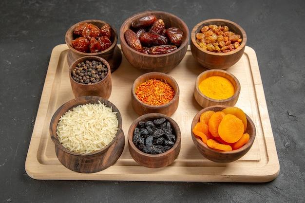 Vorderansicht verschiedene rosinen khurma und andere trockenfrüchte auf grauer oberfläche trockenfrüchtemehl sauer
