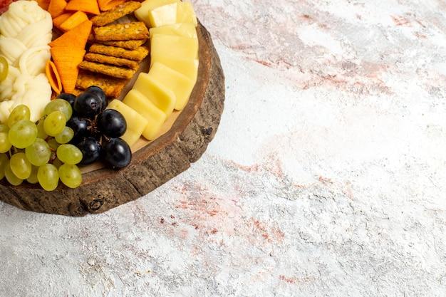 Vorderansicht verschiedene snacks cips würstchen käse und frische trauben auf leerraum