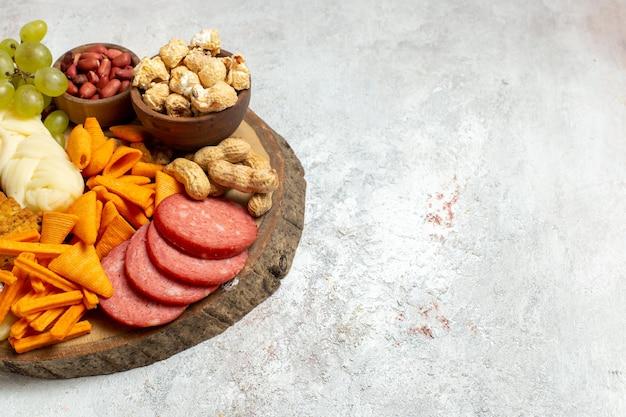 Vorderansicht verschiedene snacks nüsse cips käse und würstchen auf weißen boden nuss snack mahlzeit essen